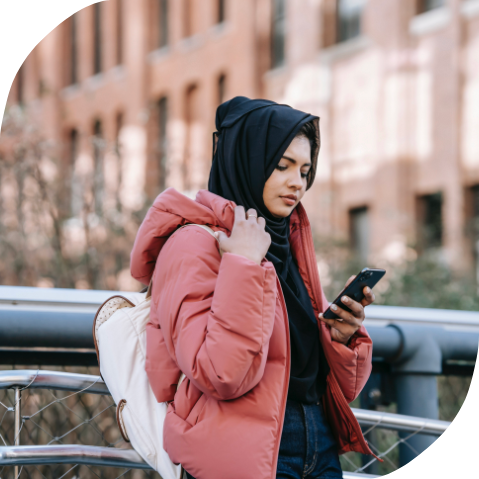 A young Muslim woman walking outside and checking her phone. She is wearing a black hijab and a red winter coat.