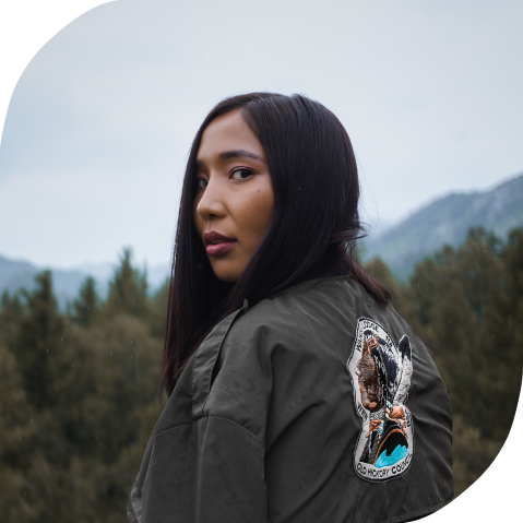 A young Indigenous woman glances over her shoulder on a cloudy day. Behind her are mountains and a forest.