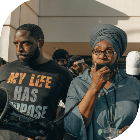 """A Black man holding a megaphone in a crowd. He is wearing a shirt that says, """"My life has purpose."""" A Black woman next to him is speaking into the microphone. She is wearing a blue turban and glasses."""
